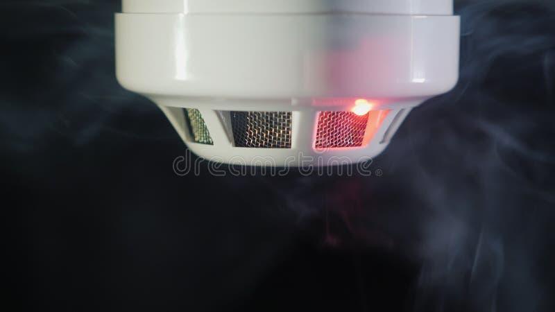 El detector de humo es accionado por un chorrito del dum, los indicadores luminosos rojos para arriba imagen de archivo libre de regalías