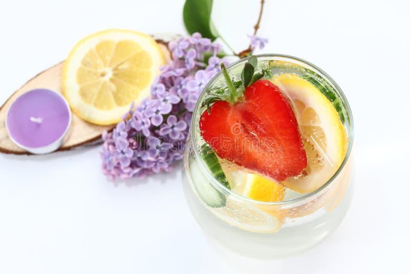 El Detox condimentó el agua con el limón, el pepino y la fresa en el fondo blanco con la lila y la decoración de madera Concepto  fotos de archivo