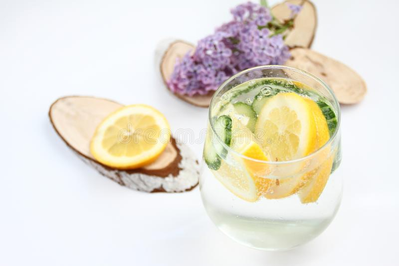 El Detox condimentó el agua con el limón y el pepino en el fondo blanco con la decoración de la lila y de madera Concepto sano de fotografía de archivo