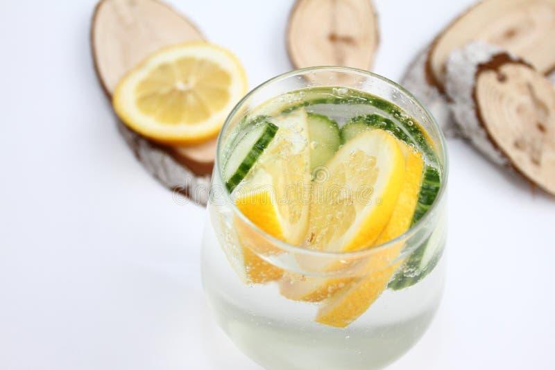 El Detox condimentó el agua con el limón y el pepino en el fondo blanco con la decoración de madera Concepto sano del alimento imagenes de archivo