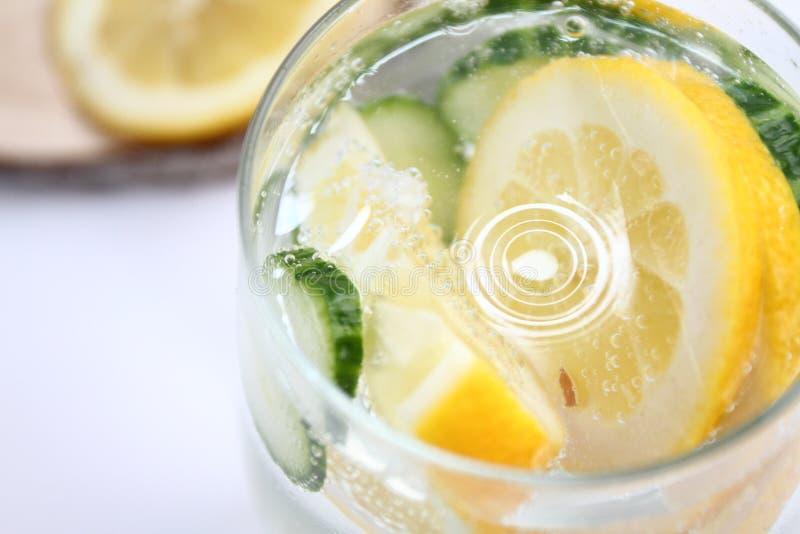 El Detox condimentó el agua con el limón y el pepino en el fondo blanco con la decoración de madera Concepto sano del alimento fotografía de archivo