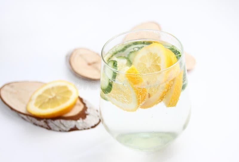 El Detox condimentó el agua con el limón y el pepino en el fondo blanco con la decoración de madera Concepto sano del alimento imagen de archivo