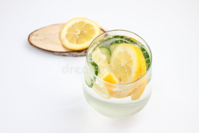 El Detox condimentó el agua con el limón y el pepino en el fondo blanco con la decoración de madera Concepto sano del alimento fotos de archivo