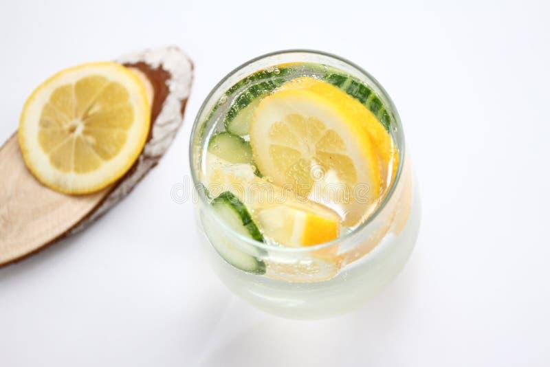 El Detox condimentó el agua con el limón y el pepino en el fondo blanco con la decoración de madera Concepto sano del alimento foto de archivo libre de regalías