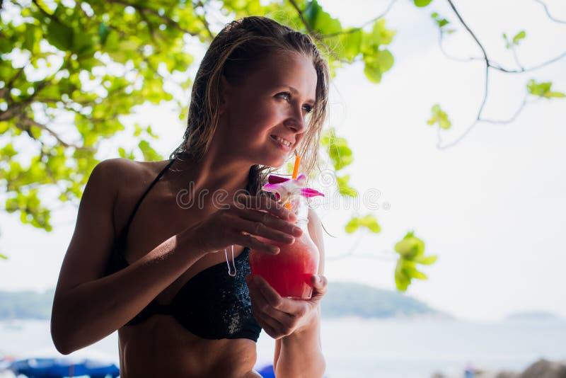 El Detox limpia a la mujer vegetal del smoothie Consumición del bikini de la mujer sana del deporte que lleva fresca y feliz desp foto de archivo