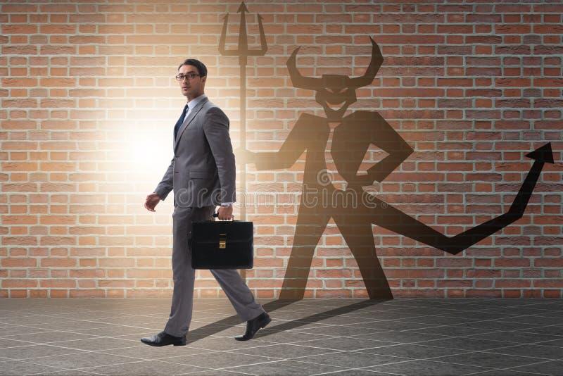 El diablo que oculta en el hombre de negocios - concepto del alter ego foto de archivo