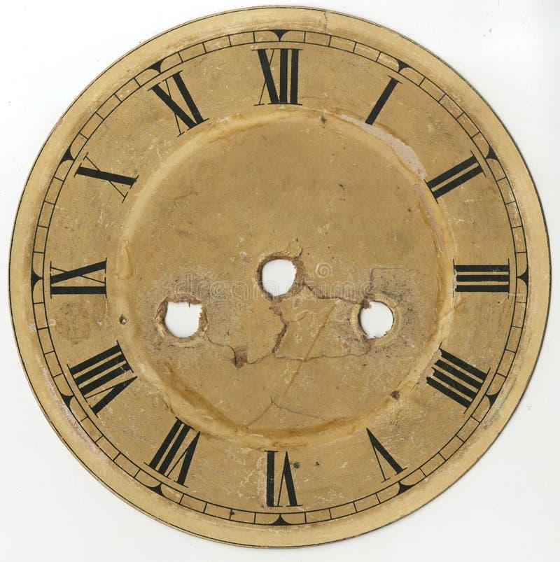 El dial del reloj viejo con los números romanos y sin las flechas, con los agujeros para el mecanismo y las llaves de la planta y imagenes de archivo