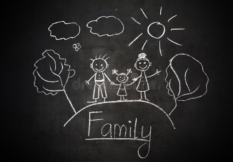 El dibujo del niño con tiza en la familia feliz de la pizarra de la escuela imágenes de archivo libres de regalías