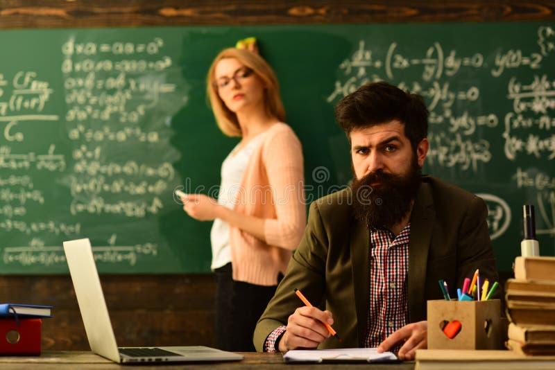 El dibujo del profesor en la sala de clase en la escuela, estudiantes universitarios que estudian con los libros en la biblioteca imagen de archivo