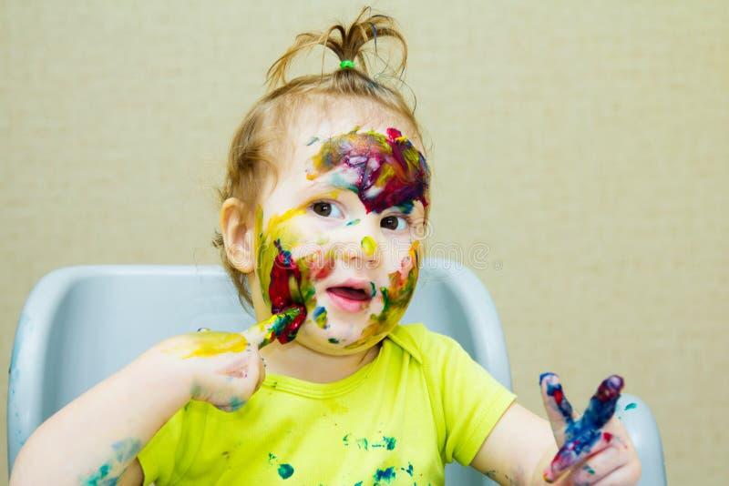 El dibujo hermoso de la niña en el álbum, la cara manchada y la pintura de las manos, observa foto de archivo libre de regalías