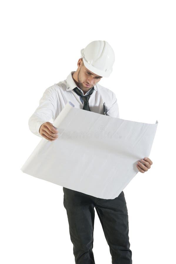 El dibujo hermoso joven de la lectura del técnico de la construcción planea en blanco imágenes de archivo libres de regalías