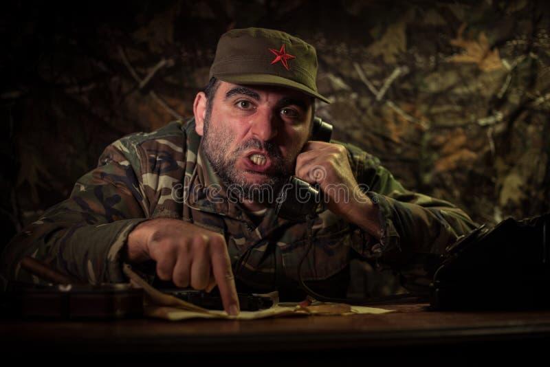 El dictador malvado que se sienta en la tabla Sentada general comunista enojada en la sede o el comandante cubano en sitio oscuro imágenes de archivo libres de regalías