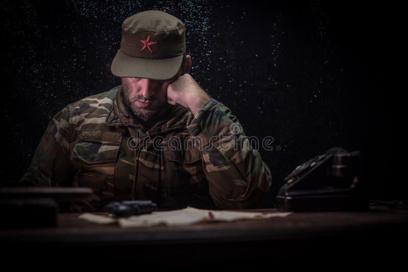 El dictador malvado que se sienta en la tabla Sentada general comunista enojada en la sede o el comandante cubano en sitio oscuro foto de archivo libre de regalías