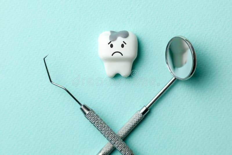 El diente blanco con la carie está triste en las herramientas verdes espejo, gancho del fondo y del dentista de la menta fotos de archivo