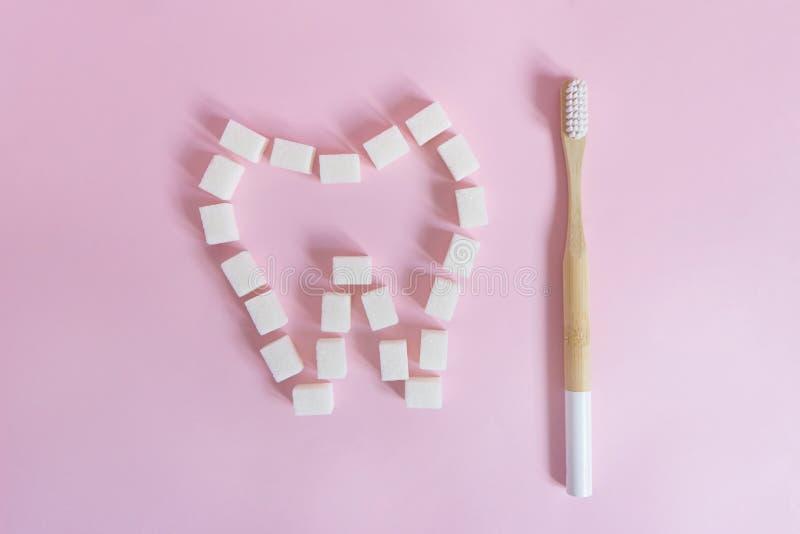 El diente se alinea con los cubos del azúcar blanco en un fondo rosado al lado de un cepillo de dientes de bambú imágenes de archivo libres de regalías