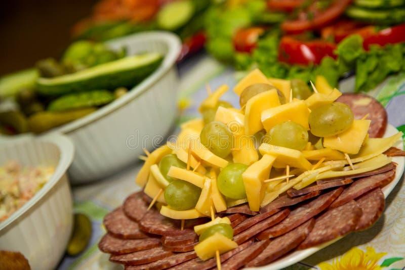 El diferente tipo de salchicha y el jamón se presentan en una placa con queso y uvas fotografía de archivo