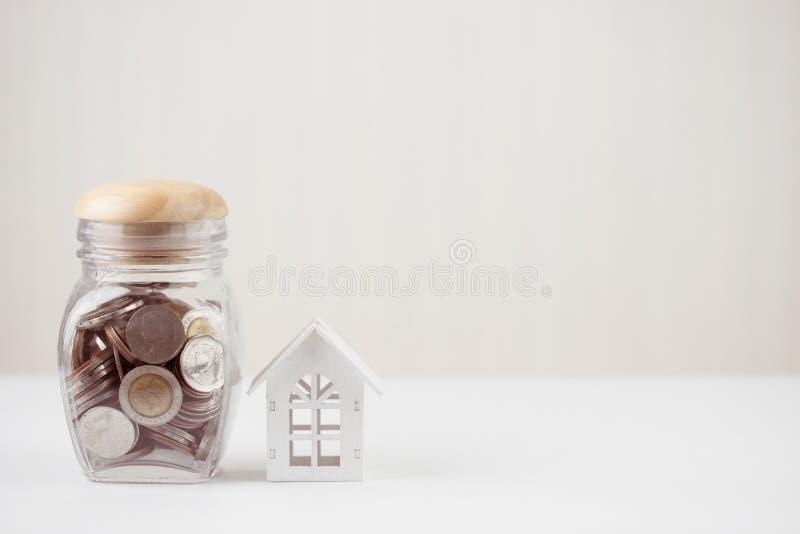 El dinero de ahorros acuña en el tarro de cristal con la casa blanca modelo en la tabla de madera Inversión de la propiedad e hip fotos de archivo libres de regalías