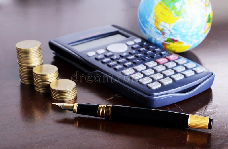 El dinero de la calculadora acuña con la pluma y la tierra para el mone del préstamo imágenes de archivo libres de regalías