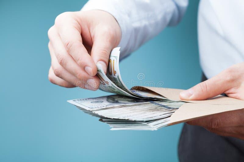 El dinero de la cuenta del hombre de negocios aprovecha su mano La economía, ahorro, sueldo y dona concepto imagen de archivo