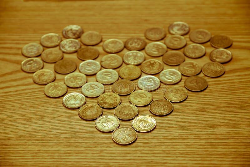 El dinero de la moneda colocado en una tabla de madera es en forma de corazón, amor Valent imagenes de archivo