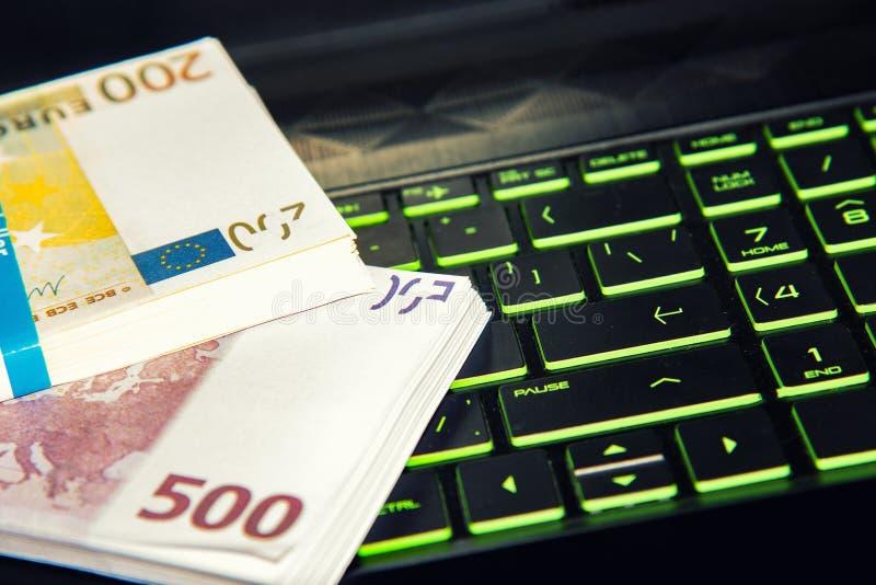 El dinero en un ordenador portátil, los paquetes de dólares y los euros están en el teclado de un ordenador portátil, el concepto foto de archivo