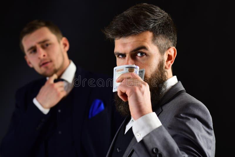 El dinero no tiene ningún olor Hombre barbudo con el dinero del efectivo Compañeros de trabajo o colegas acertados Los socios com imagen de archivo