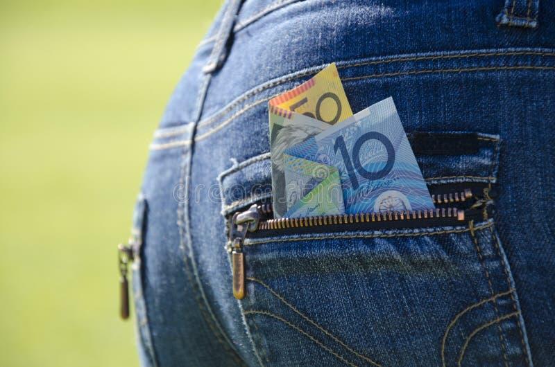 El dinero que mira furtivamente fuera de los tejanos detrás embolsa fotografía de archivo libre de regalías