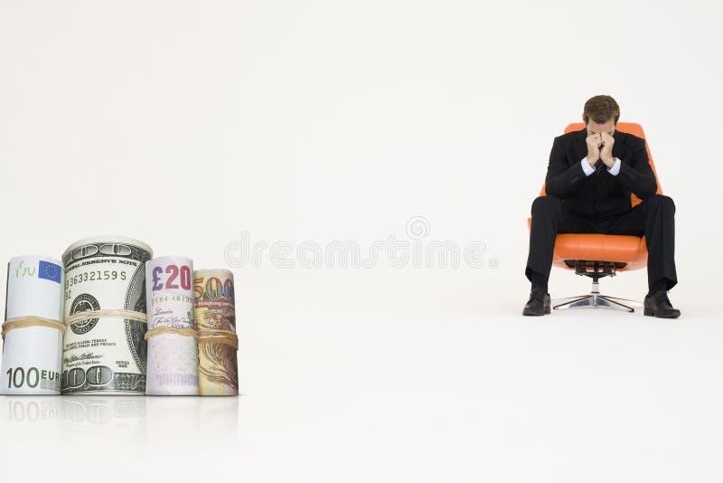 El dinero rueda con el hombre de negocios preocupante en la silla que representa problemas financieros fotos de archivo libres de regalías