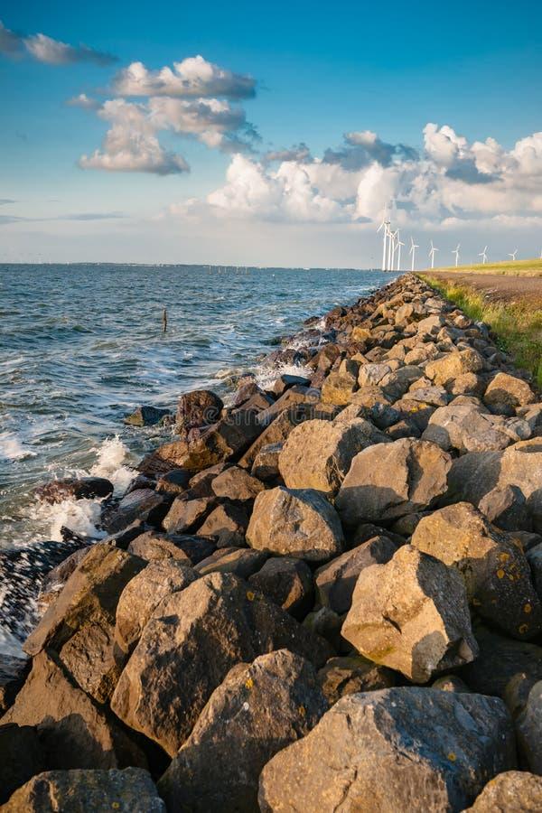 El dique del pólder con los bolardos de piedra a lo largo del Ijsselmeer en Flev foto de archivo