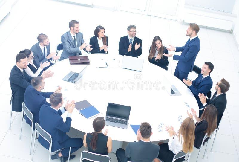 El director de las finanzas está detrás de una mesa redonda grande y dice el sha imagen de archivo