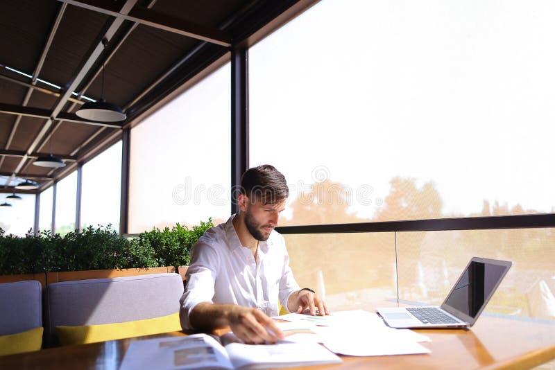 El director de marketing trabaja con los documentos y el ordenador portátil de la estadística en t fotos de archivo libres de regalías