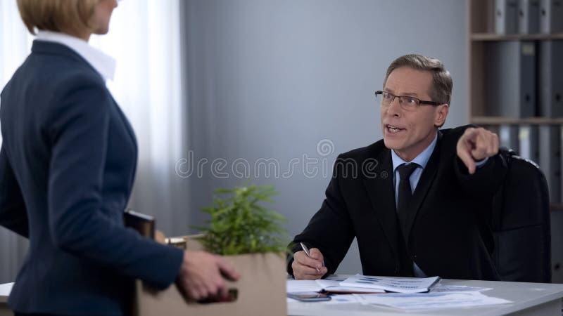 El director de sexo masculino despide al ayudante, trabajador no profesional incompetente, despido foto de archivo libre de regalías