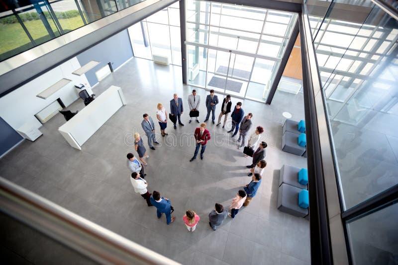 El director joven celebra la reunión con su equipo en círculo en pasillo de la compañía imágenes de archivo libres de regalías