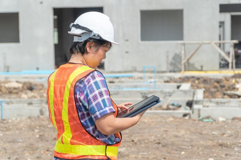 El dirigir asiático de las mujeres sostiene una tableta para el uso en la inspección de los emplazamientos de la obra para la exa fotos de archivo libres de regalías
