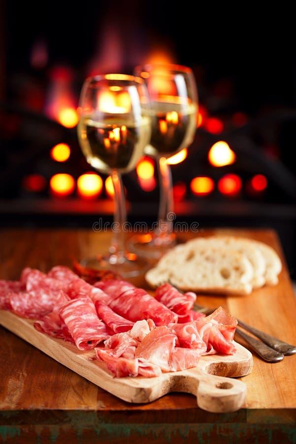 El disco del jamon del serrano curó la carne con la chimenea y el vino acogedores foto de archivo libre de regalías