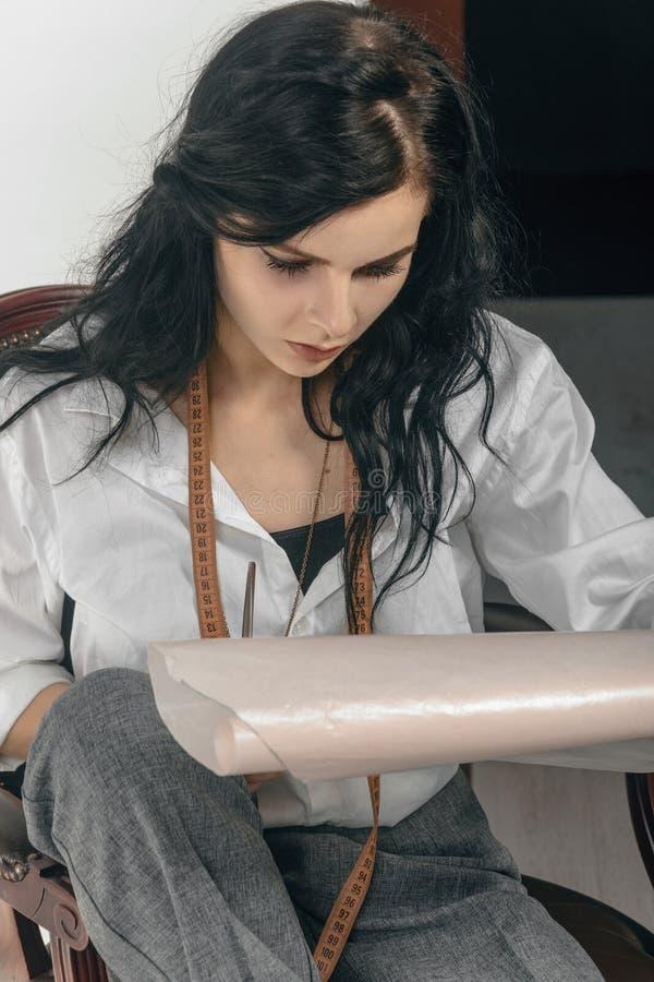 El diseñador de moda hace bosquejos en el papel de trazo imagen de archivo