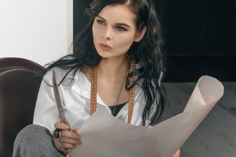 El diseñador de moda hace bosquejos en el papel de trazo imagen de archivo libre de regalías