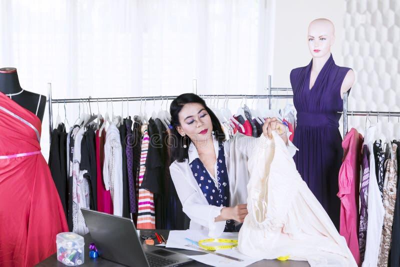 El diseñador de moda de sexo femenino joven sostiene una tela foto de archivo