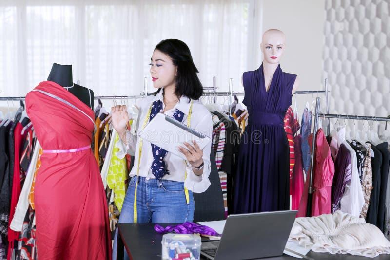 El diseñador de moda de sexo femenino trabaja con la tableta foto de archivo libre de regalías