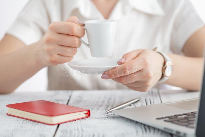 El diseñador de sexo femenino da sostener la taza de bebida caliente y el trabajo de los wi foto de archivo