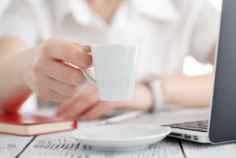 El diseñador de sexo femenino da sostener la taza de bebida caliente y el trabajo de los wi fotografía de archivo libre de regalías