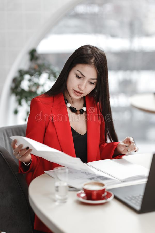 El diseñador elegante de la mujer joven está trabajando en el proyecto de diseño de la sentada interior en el escritorio con el o imagenes de archivo