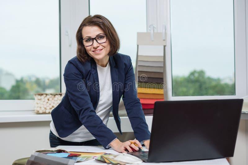El diseñador o el arquitecto que le presenta y que mira trabaja con las muestras de telas para las cortinas y las persianas, vent imagen de archivo