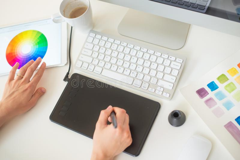 El diseñador web gráfico hace el trabajo usando una tableta de gráficos, mesa imagen de archivo
