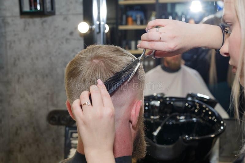 El dise?ar profesional del pelo del peluquero de su cliente El amo proporciona un corte de pelo fotografía de archivo