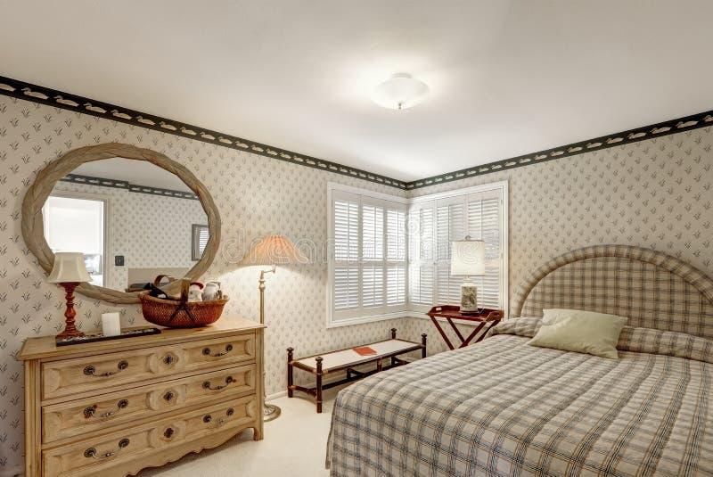 El diseño acogedor del dormitorio en tonos grises ofrece las paredes empapeladas hierba beige fotografía de archivo libre de regalías