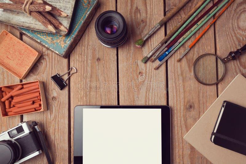 El diseño del jefe del sitio web con la tableta digital y el vintage creativo se opone foto de archivo