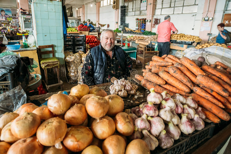 El distribuidor autorizado georgiano rechoncho maduro del hombre de verduras se está sentando en el Co fotos de archivo libres de regalías
