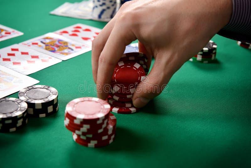 El distribuidor autorizado recoge las fichas de póker rojas foto de archivo libre de regalías
