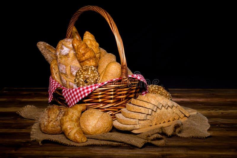 El diverso pan fresco tal como bollo del sésamo, baguette, rollos cocidos, cruasán, bollo redondo y grano entero cortó el pan fotos de archivo